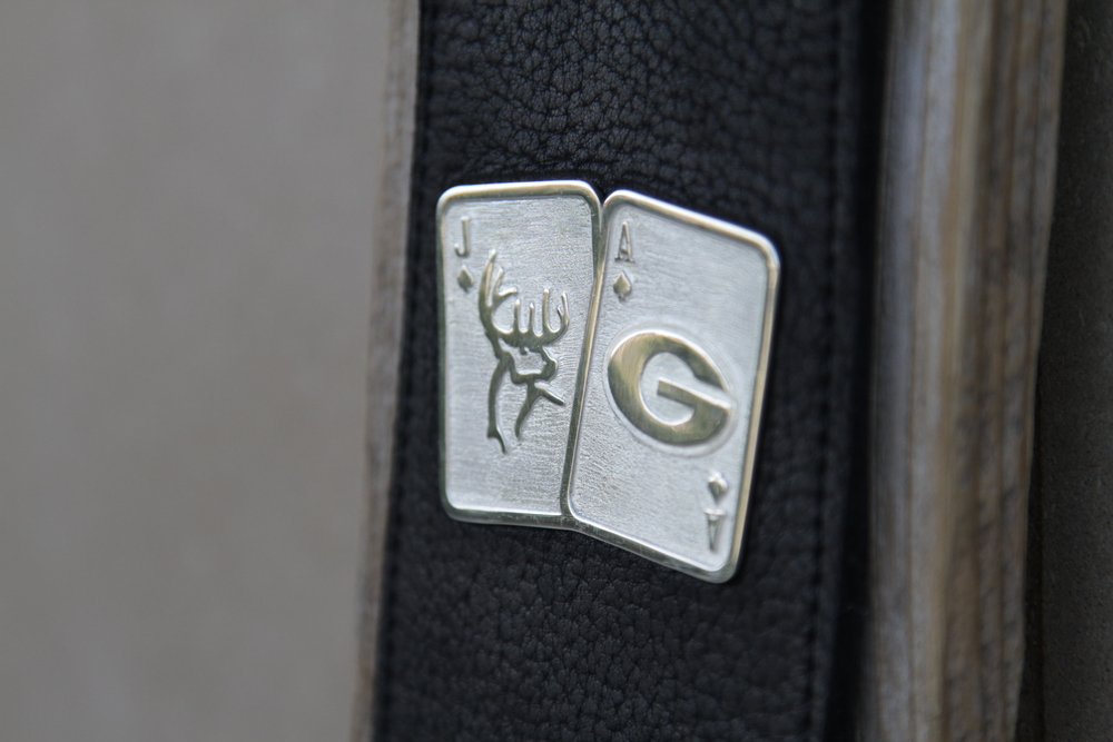 This custom, double-sided, guitar strap lapel was created for Jason Aldean during his Burn it Down Tour when he came to the BOK Center on April 10, 2015.  It was hand-crafted in sterling silver and then riveted to a Red Monkey buffalo hide guitar strap. The front features the traditional Jack and Ace logo with a twist, incorporating Jason's love of hunting and the Georgia Bulldogs, and the back features his traditional logo.