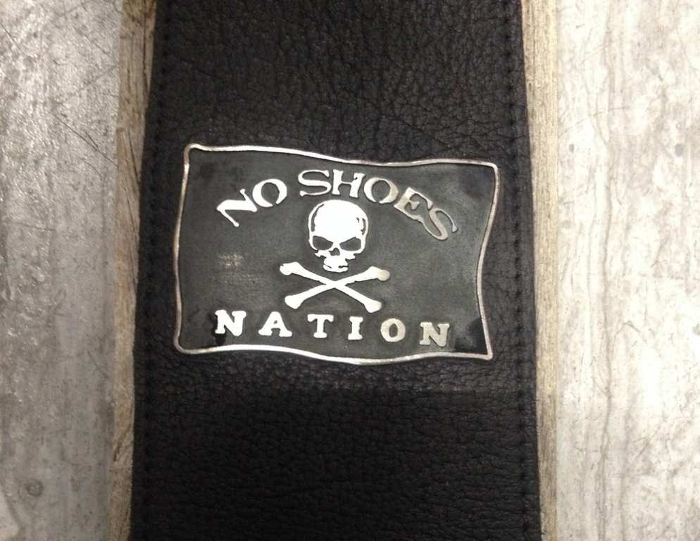 This custom, double-sided, guitar strap lapel was created for Kenny Chesney during The Big Revival Tour when he came to the BOK Center on May 14, 2015.  It was hand-crafted in sterling silver and then riveted to a Red Monkey guitar strap. With inspiration from Kenny's love of the beach and his